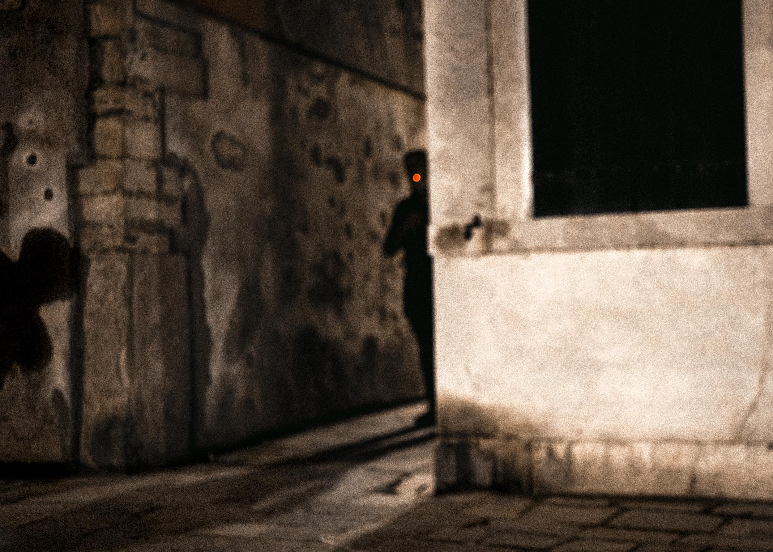 Shade of man hidden in a street at night