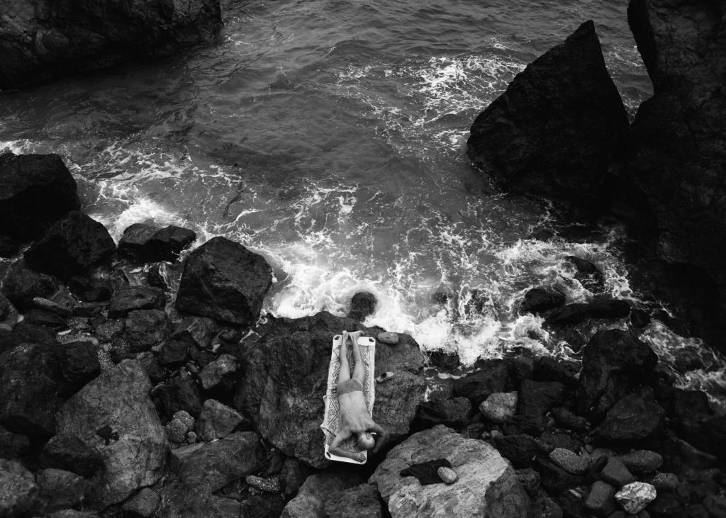 man lying on the rocks on the rocky seashore